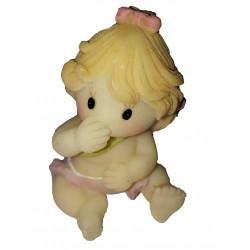Figurine miniature petite fille assise par terre se touchant la bouche